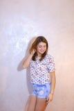 Όμορφη γυναίκα με την τοποθέτηση χαμόγελου στη κάμερα, που στέκεται στο υπόβαθρο Στοκ Φωτογραφία