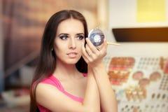 Όμορφη γυναίκα με τη βούρτσα σύνθεσης που κοιτάζει σε έναν καθρέφτη Στοκ φωτογραφίες με δικαίωμα ελεύθερης χρήσης