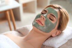 Όμορφη γυναίκα με τη μάσκα στη χαλάρωση προσώπου στοκ φωτογραφία με δικαίωμα ελεύθερης χρήσης