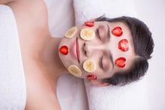 Όμορφη γυναίκα με τη μάσκα φρούτων στο πρόσωπό της Στοκ Εικόνα