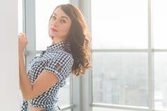 Όμορφη γυναίκα με τη μακριά χαλαρή τρίχα που στέκεται δίπλα στον τοίχο στο ευρύχωρο ελαφρύ δωμάτιο, τοποθέτηση, που εξετάζει τη κ στοκ φωτογραφίες με δικαίωμα ελεύθερης χρήσης