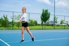 Όμορφη γυναίκα με τη ρακέτα αντισφαίρισης στο γήπεδο αντισφαίρισης στοκ εικόνες