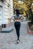 Όμορφη γυναίκα με τη σκοτεινή τρίχα στην αθλητική τοποθέτηση κοστουμιών στην οδό στοκ εικόνες