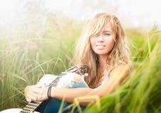 Όμορφη γυναίκα με τη συνεδρίαση κιθάρων στη χλόη. στοκ εικόνες