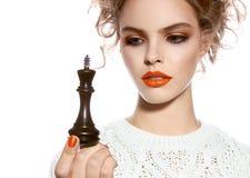 Όμορφη γυναίκα με τη σύνθεση βραδιού που κρατά ένα κομμάτι σκακιού βασιλιάδων Στοκ Φωτογραφία