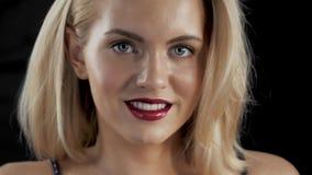 Όμορφη γυναίκα με τη φωτεινή σύνθεση γοητείας Κόκκινα χείλια και καρφιά ξανθό τρίχωμα Καθαρό δέρμα Σκοτεινό backgroud, προκλητικό απόθεμα βίντεο