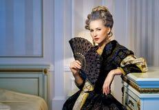 Όμορφη γυναίκα με τον ανεμιστήρα στο ιστορικό φόρεμα στο μπαρόκ ύφος μέσα Στοκ φωτογραφία με δικαίωμα ελεύθερης χρήσης