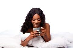 Όμορφη γυναίκα με τον εύγευστο καφέ στο κρεβάτι Στοκ Εικόνα