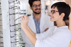 Όμορφη γυναίκα με τον οπτικό που δοκιμάζει eyeglasses Στοκ εικόνες με δικαίωμα ελεύθερης χρήσης