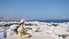 Όμορφη γυναίκα με το έξυπνο τηλέφωνο υπαίθρια στις παλαιές οδούς μια Μύκονος Κορίτσι στην οδό του χαρακτηριστικού ελληνικού παραδ φιλμ μικρού μήκους