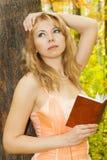 Όμορφη γυναίκα με το βιβλίο κοντά στο δέντρο Στοκ Εικόνες