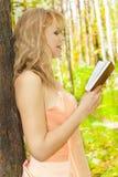 Όμορφη γυναίκα με το βιβλίο στον κήπο. Ημέρα ήλιων Στοκ Εικόνα