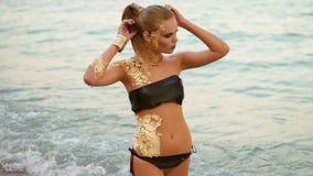 Όμορφη γυναίκα με το επαγγελματικό χρυσό makeup που στέκεται στο νερό στην παραλία, που κοιτάζει στη κάμερα Προκλητικός φιλμ μικρού μήκους