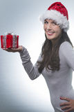 Όμορφη γυναίκα με το καπέλο Santa που αντέχει ένα δώρο Στοκ φωτογραφία με δικαίωμα ελεύθερης χρήσης