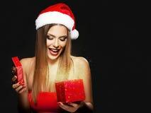 Όμορφη γυναίκα με το καπέλο Santa ` s που ανοίγει ένα παρόν στοκ εικόνες