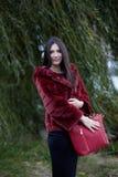 Όμορφη γυναίκα με το κόκκινες παλτό και την τσάντα Στοκ Φωτογραφίες