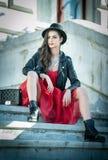 Όμορφη γυναίκα με το μαύρο καπέλο, το κόκκινες φόρεμα και τις μπότες που θέτουν τη συνεδρίαση στα σκαλοπάτια Νέος χρόνος εξόδων b Στοκ Εικόνες
