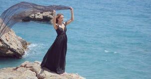 Όμορφη γυναίκα με το μαύρο μαντίλι στο κομψό μαύρο φόρεμα απόθεμα βίντεο