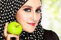 Όμορφη γυναίκα με το μαύρο μαντίλι που κρατά το πράσινο μήλο Στοκ Εικόνες