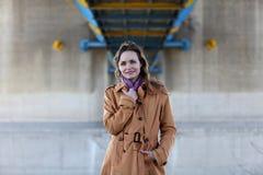 Όμορφη γυναίκα με το μπεζ παλτό που στέκεται κάτω από μια γέφυρα Στοκ εικόνες με δικαίωμα ελεύθερης χρήσης