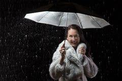 Όμορφη γυναίκα με το παλτό γουνών που στέκεται στη βροχή κάτω από μια ομπρέλα Στοκ Εικόνες