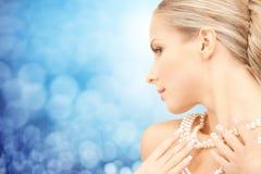Όμορφη γυναίκα με το περιδέραιο μαργαριταριών θάλασσας πέρα από το μπλε Στοκ Εικόνα