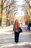 Όμορφη γυναίκα με το πορτοκάλι στο πάρκο στην πτώση στοκ φωτογραφία