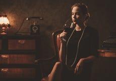 Όμορφη γυναίκα με το ποτήρι του κρασιού στο αναδρομικό εσωτερικό Στοκ Φωτογραφία