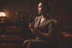 Όμορφη γυναίκα με το ποτήρι του κρασιού στο αναδρομικό εσωτερικό Στοκ εικόνες με δικαίωμα ελεύθερης χρήσης