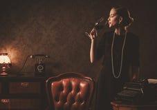 Όμορφη γυναίκα με το ποτήρι του κρασιού στο αναδρομικό εσωτερικό Στοκ εικόνα με δικαίωμα ελεύθερης χρήσης