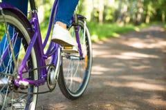 Όμορφη γυναίκα με το ποδήλατο στο πάρκο πόλεων όμορφη φύση Στοκ Φωτογραφίες
