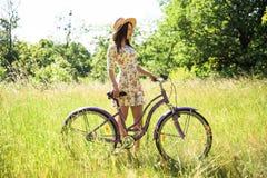 Όμορφη γυναίκα με το ποδήλατο στο πάρκο πόλεων όμορφη φύση Στοκ Εικόνες