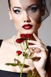 Όμορφη γυναίκα με το σκούρο κόκκινο λουλούδι τριαντάφυλλων στην αναδρομική γοητεία πέπλων Στοκ Εικόνες