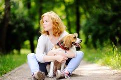 Όμορφη γυναίκα με το σκυλί λαγωνικών στο πάρκο Στοκ φωτογραφία με δικαίωμα ελεύθερης χρήσης