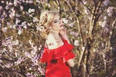 Όμορφη γυναίκα με το τέλειο υγιές πορτρέτο δερμάτων Θηλυκό κορίτσι μόδας σχετικά με το πρόσωπό της στον ανθίζοντας κήπο κοντά επά Στοκ εικόνες με δικαίωμα ελεύθερης χρήσης