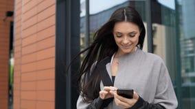 Όμορφη γυναίκα με το τηλέφωνο κοντά στο επιχειρησιακό κέντρο απόθεμα βίντεο
