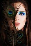 Όμορφη γυναίκα με το φτερό Makeup και Peacock στοκ εικόνα