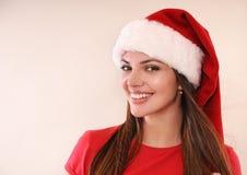 Όμορφη γυναίκα με το χαριτωμένο χαμόγελο στο καπέλο Santa ευτυχές για τα Χριστούγεννα στοκ εικόνα με δικαίωμα ελεύθερης χρήσης