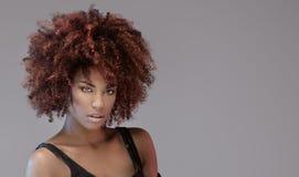 Όμορφη γυναίκα με το afro hairstyle που θέτει στοκ φωτογραφία