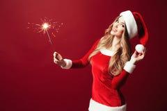 Όμορφη γυναίκα με το sparkler στο κόκκινο σκηνικό στοκ φωτογραφίες