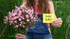 Όμορφη γυναίκα με χρόνια πολλά την κάρτα και τα ροζ λουλούδια απόθεμα βίντεο