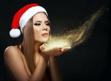 Όμορφη γυναίκα με Santa& x27 καπέλο του s, φυσώντας χρυσή σκόνη Στοκ Εικόνα