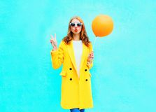 Όμορφη γυναίκα μόδας με ένα μπαλόνι αέρα σε ένα κίτρινο παλτό στοκ φωτογραφίες με δικαίωμα ελεύθερης χρήσης