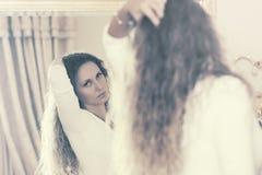 Όμορφη γυναίκα μόδας με τις μακριές σγουρές τρίχες που κοιτάζει στον καθρέφτη Στοκ εικόνες με δικαίωμα ελεύθερης χρήσης