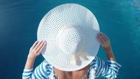 Όμορφη γυναίκα μόδας που φορά το άσπρο καπέλο κομψότητας και που απολαμβάνει την ηλιοθεραπεία στις θερινές διακοπές απόθεμα βίντεο