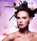 Όμορφη γυναίκα μόδας με τα ρόδινα λουλούδια στις τρίχες Στοκ Φωτογραφίες