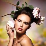 Όμορφη γυναίκα μόδας με τα ρόδινα λουλούδια στις τρίχες Στοκ εικόνα με δικαίωμα ελεύθερης χρήσης
