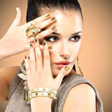Όμορφη γυναίκα μόδας με το μαύρο makeup και το χρυσό μανικιούρ Στοκ Φωτογραφίες