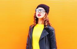 Όμορφη γυναίκα μόδας στο σακάκι μαύρων καπέλων και βράχου πέρα από το ζωηρόχρωμο πορτοκάλι Στοκ εικόνα με δικαίωμα ελεύθερης χρήσης