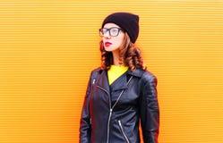 Όμορφη γυναίκα μόδας στο σακάκι μαύρων καπέλων και βράχου πέρα από το ζωηρόχρωμο πορτοκαλί υπόβαθρο Στοκ Εικόνα